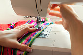 Woman's hands in the process of sewing a colored cloth on the sewing machine