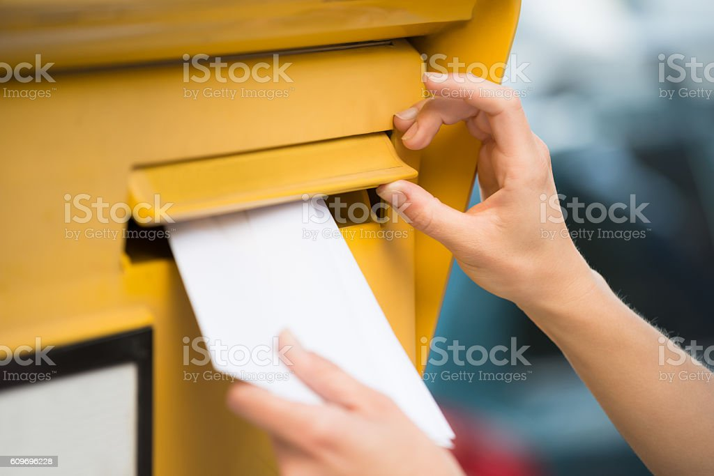 Woman's Hands Inserting Letter In Mailbox stock photo