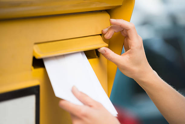 woman's hands inserting letter in mailbox - mail stock photos and pictures
