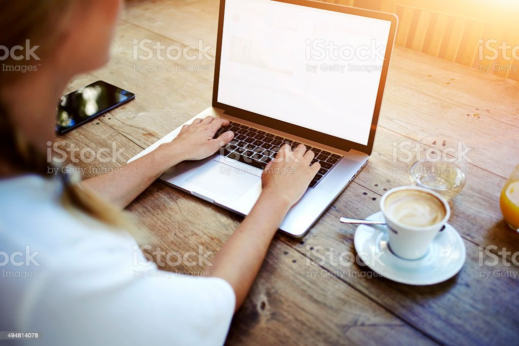 Woman's hands keyboarding on net-book while sitting in cafe stock photo