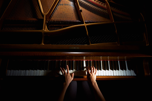 Woman's hands on the keyboard of the piano in night