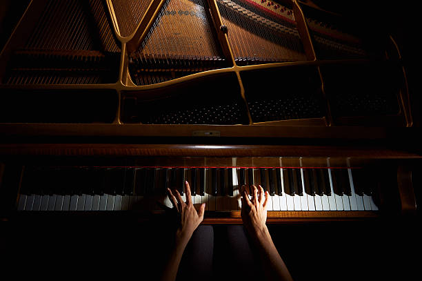 Woman's hands on the keyboard of the piano in night Woman's hands playing on the keyboard of the piano in night closeup pianist stock pictures, royalty-free photos & images