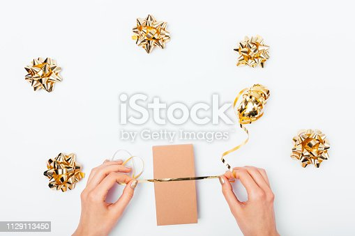 Woman's hands packing gift box with golden ribbon next to shiny bows on white table, top view.