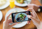 Woman's hands photograph her meal with her mobile phone