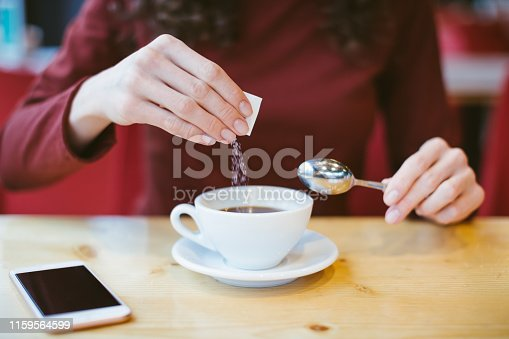istock Woman's hands pouring sugar into black coffee - girl sitting at the table with espresso and smartphone - blood and glycemic index control for diabetes -excess of white sugar in food concept 1159564599