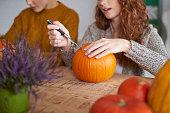 Woman's hands preparing decorations for Halloween