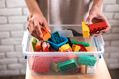 Woman's hands putting colored blocks into plastic box. Close up.