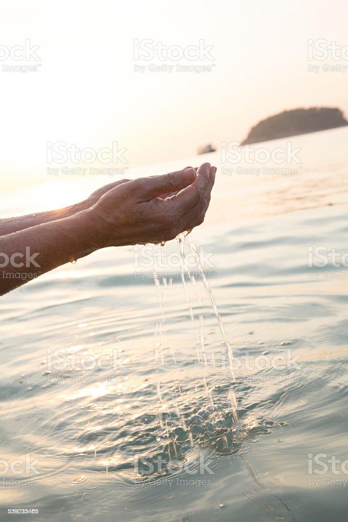 Woman's hands cuchara de agua de mar foto de stock libre de derechos