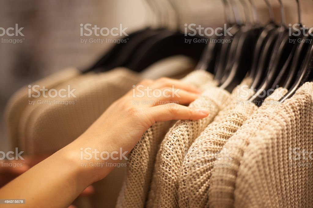 Woman's Hands Selecting Sweater in Fashion Store stock photo