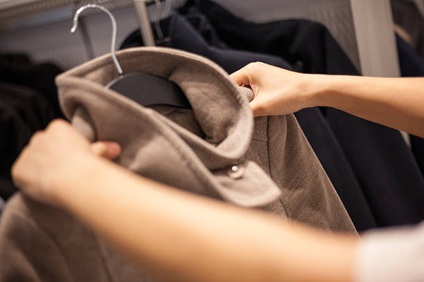 woman's hands auswahl wintermantel in mode speichern - wintermantel damen wolle stock-fotos und bilder