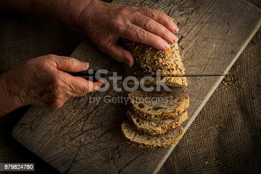 istock Woman's hands slicing homemade bread. 879824780
