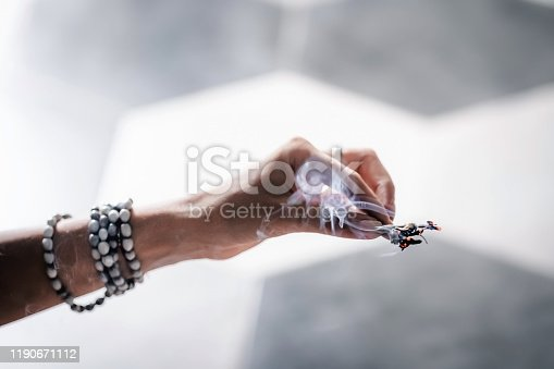 Woman's hands smudging burning sage, dry plant. Space, energy healing. Close up, copy space