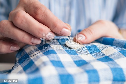 istock Woman's hands stitching button on a shirt in tailor shop, close up view 1134327803