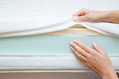 istock Woman's hands touching different layers of new mattress. Checking hardness and softness. Choice of the best type and quality. Front view. Close up. 1065773092