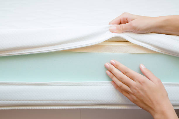 Woman's hands touching different layers of new mattress. Checking hardness and softness. Choice of the best type and quality. Front view. Close up. Woman's hands touching different layers of new mattress. Checking hardness and softness. Choice of the best type and quality. Front view. Close up. latex stock pictures, royalty-free photos & images