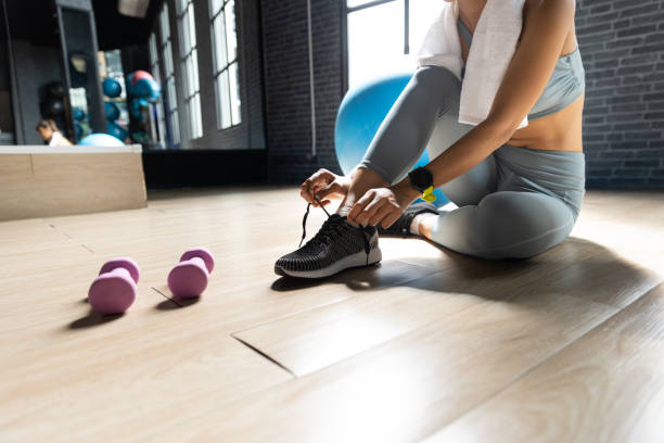 Woman's hands tying shoes Get ready to exercise at gym In a room with a window with natural light. Fitness and healthy lifestyle, Starting to exercise concept stock photo