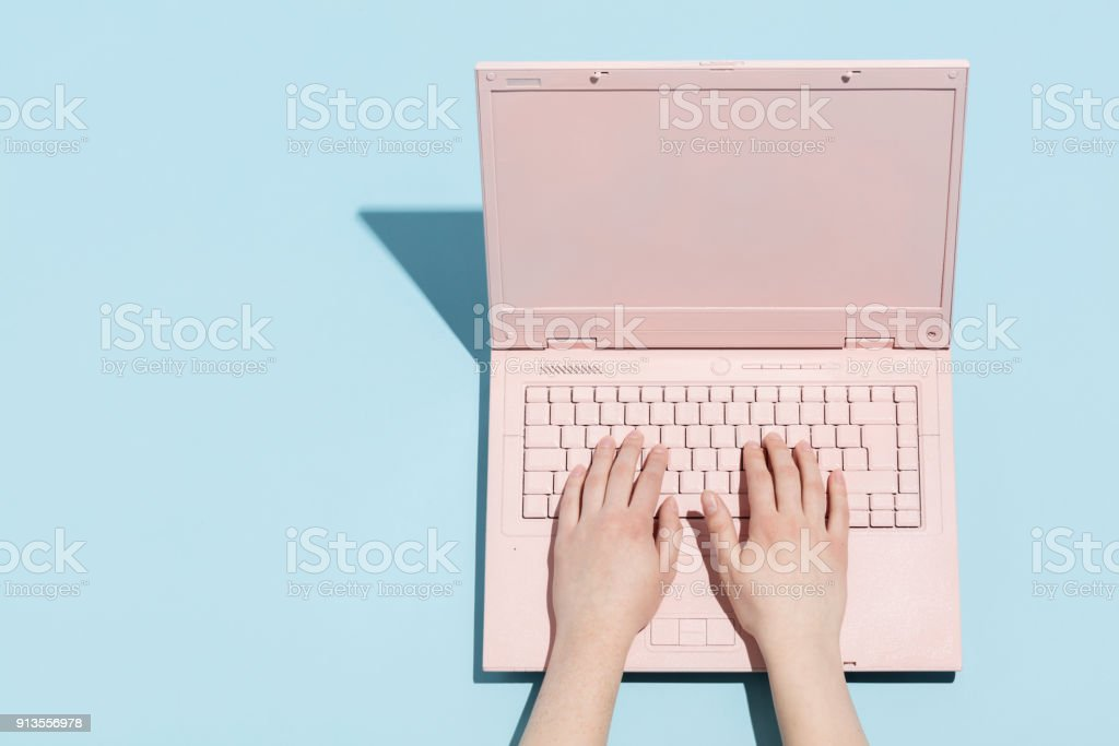 Woman's hands typing on a pastel pink keyboard stock photo