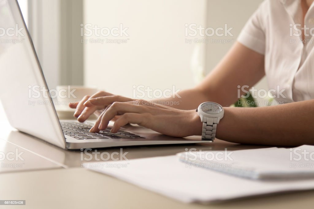 Womans hands typing on laptop at workplace stock photo