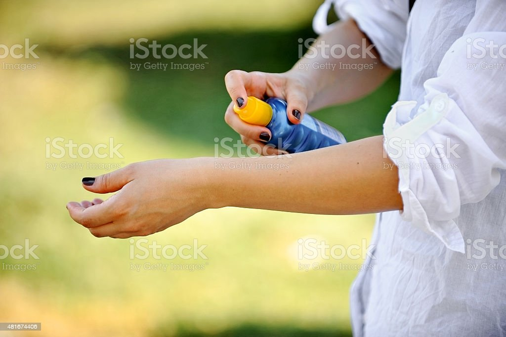 Woman's hands using sunscreen stock photo