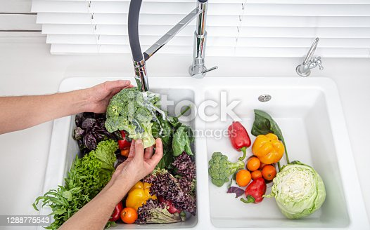 Women's hands wash vegetables in the kitchen sink of a modern kitchen. Healthy food concept.