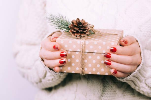 frauenhand mit weihnachts-geschenk-box - bastelkarton stock-fotos und bilder