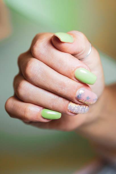frauenhände mit verzierten nägeln - nägel glitzer stock-fotos und bilder