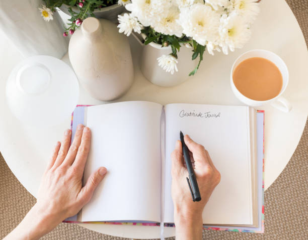 Woman's hands with gratitude journal stock photo