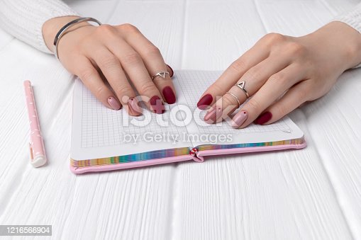 831932306 istock photo Womans hands with minimal pink spring summer manicure design on office table 1216566904