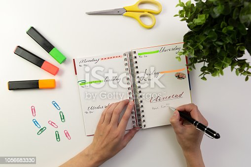 Woman's hands with pen writing in planner. Modern office desk. Working, writing concept