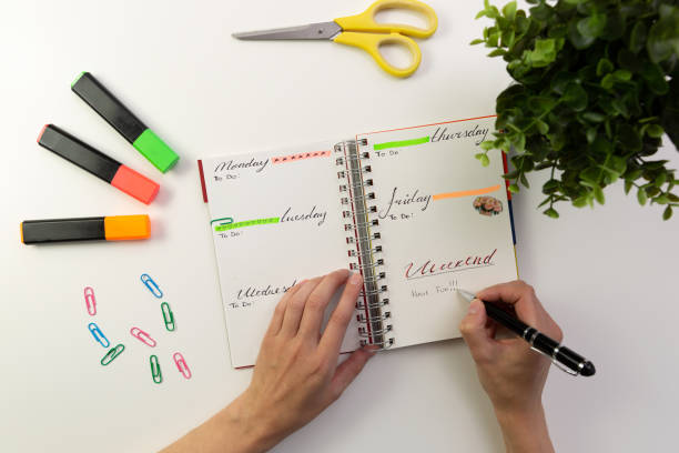 woman's hands with pen writing in planner. modern office desk. working, writing concept - diario foto e immagini stock