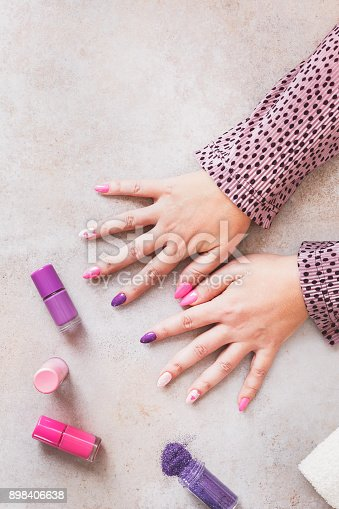 1147741037istockphoto Woman`s hands with purple and pink manicure 898406638