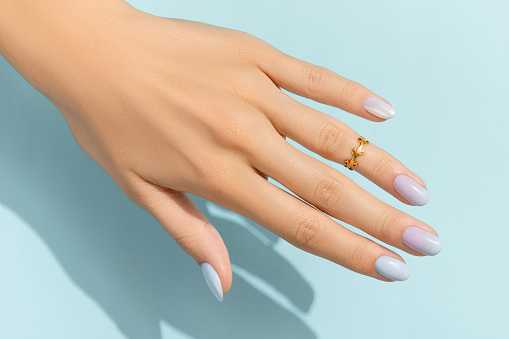 Womans hands with trendy manicure on blue background. Summer nail design. Beauty salon concept