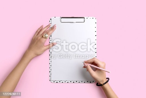 831932306 istock photo Womans hands with trendy marble manicure write on clipboard 1222626111