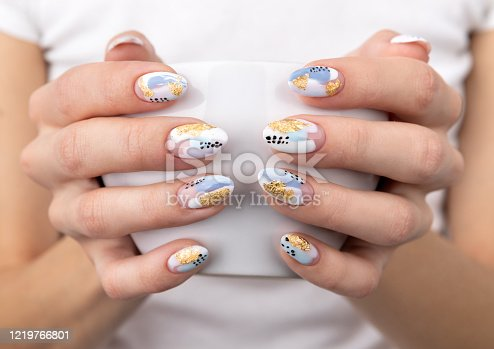 istock Woman's hands with trendy pastel color nails holding cup 1219766801
