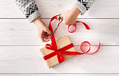 Woman's hands wrapping christmas holiday present iwith red ribbon