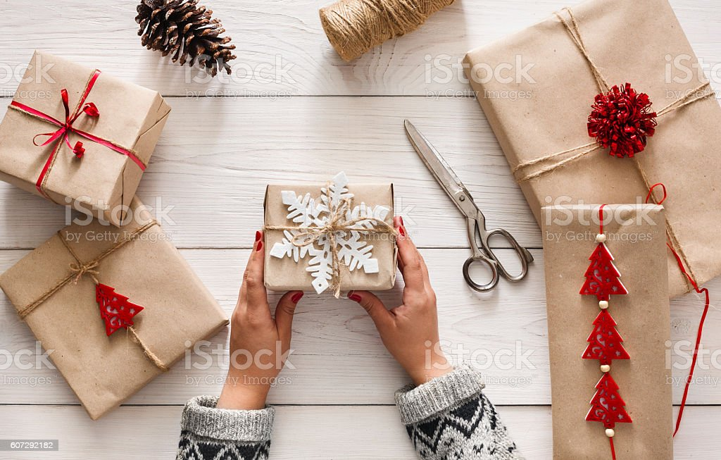 Woman's hands wrapping christmas holiday present with craft twine stock photo