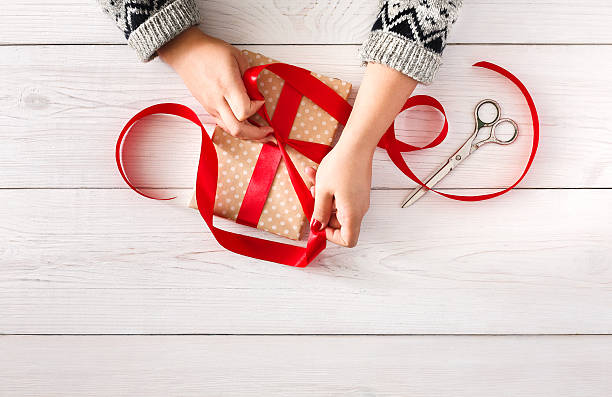 woman's hands wrapping christmas holiday present with red ribbon - bastelkarton stock-fotos und bilder