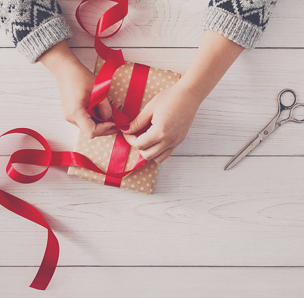 woman's hands wrapping christmas holiday present with red ribbon - winterdeko basteln stock-fotos und bilder