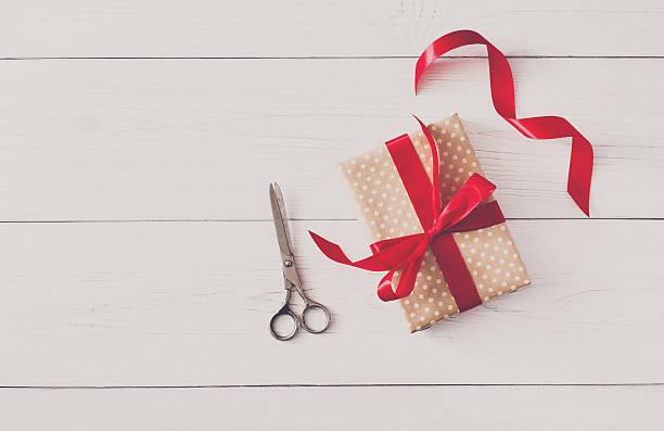 hände der frau verpackung weihnachten urlaub geschenk mit roten band - bastelkarton stock-fotos und bilder
