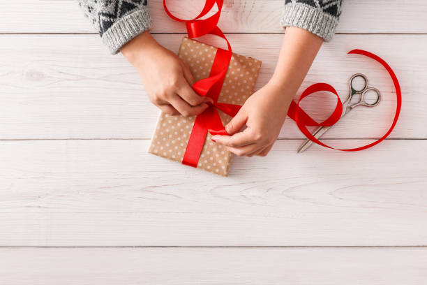 woman's hands wrapping christmas holiday present with red ribbon - wrapping paper stock photos and pictures