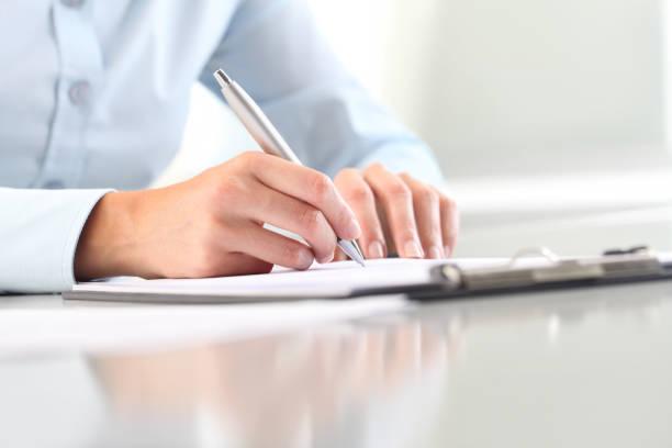 女性の手は、ペンでクリップボードにシートに書いています。机の上に隔離 ストックフォト