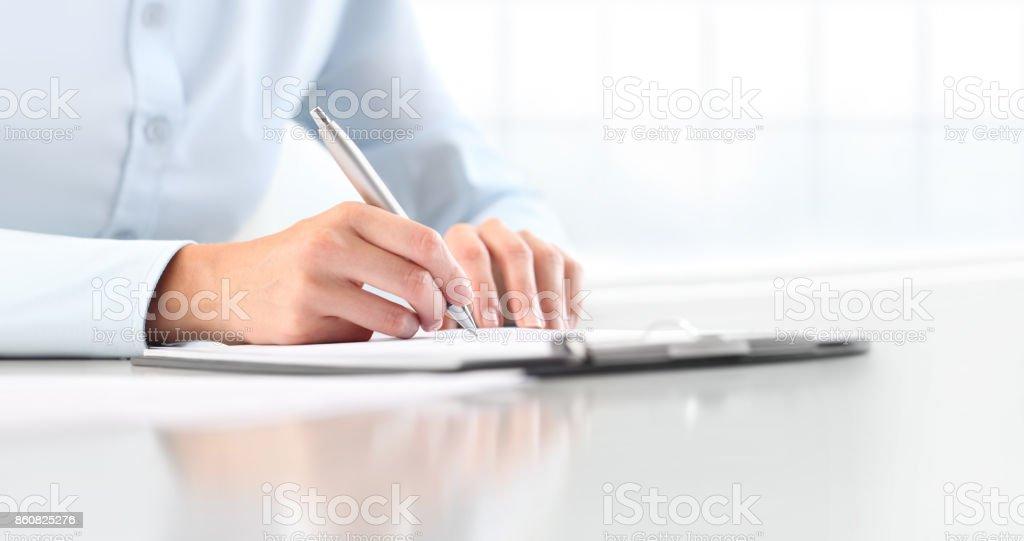 Manos de mujer escribiendo en la hoja en un portapapeles con una pluma, aislada en el escritorio - foto de stock