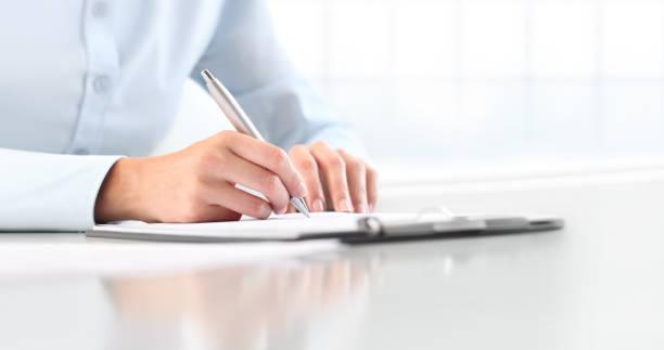 manos de mujer escribiendo en la hoja en un portapapeles con una pluma, aislada en el escritorio - gerente de cuentas fotografías e imágenes de stock