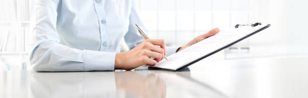 woman's hands writing on sheet  in a clipboard with a pen, isolated on desk - form document stock pictures, royalty-free photos & images