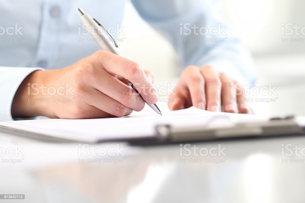 Woman's hands writing on sheet in clipboard with a pen stock photo