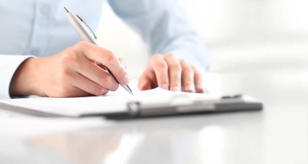 分離の机の上のペンをクリップボードに紙のシートに書く女性の手 - 書く ストックフォトと画像