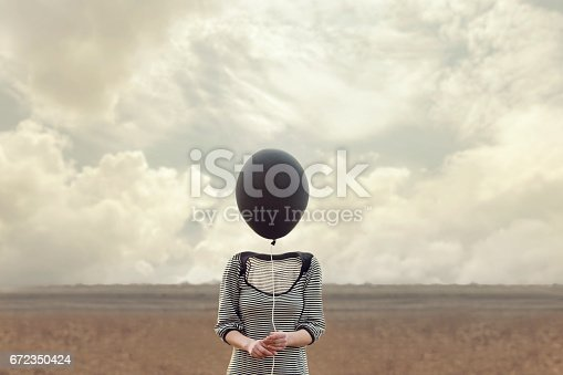861862204 istock photo woman's head replaced by a black balloon 672350424