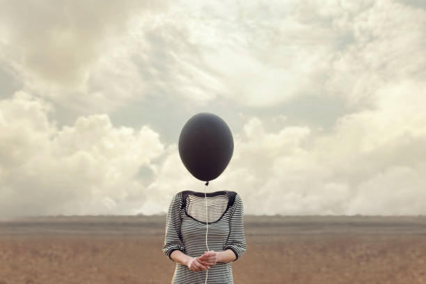 woman's head replaced by a black balloon stock photo