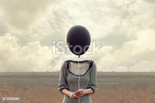 istock woman's head replaced by a black balloon 672355092