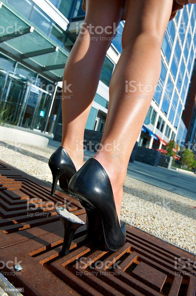Woman's high heel shoe trapped in sidewalk grate stock photo